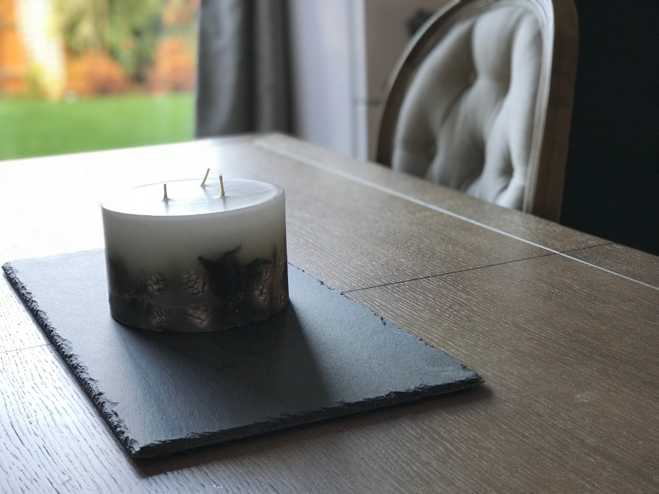 wooden dining table with 3 wick candle on top