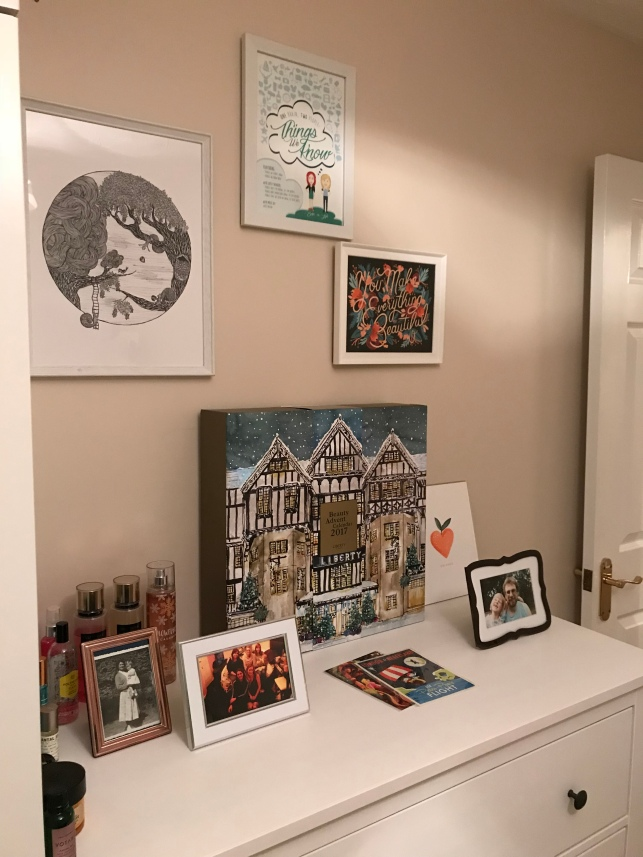 chest of drawers with photos on the wall