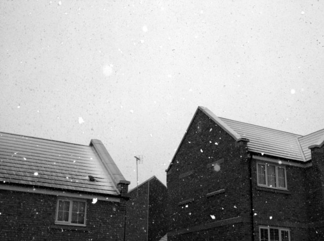 black and white photo of snowfall around housing estate