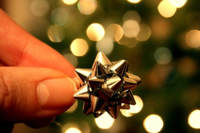 tiny gift bow held by finger