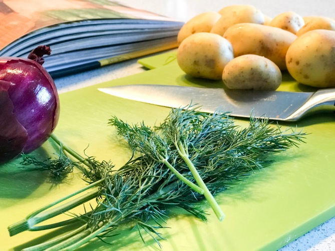 onion, dill and new potatoes on a chopping board